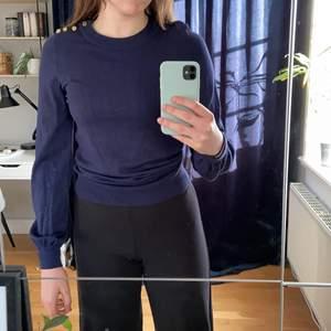 Finstickad tröja från Falsterbo X Gina tricot. Tröjan är marinblå vilket första bilden visar samt att den har guldiga knappar på vänstra axeln. Den har även lite av en ballongärm. Använd ett fåtal gånger.