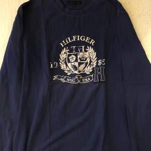 En fin långärmad Tommy Hilfiger t-shirt strl 14y navy färgad m vitt tryck. Använd i 2-3 år, gott skick och felfri! Nypris: 550kr