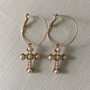 Guldiga creoler med hängande kors med pärlor. Från H&M. Aldrig använda så i utmärkt skick!