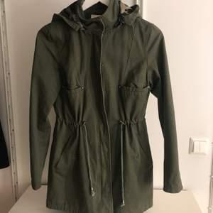 En militärgrön jacka ifrån madlady i storlek S. Jackan har militärmönster inuti och luvan går att ta bort om man vill.
