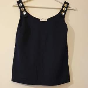 Jättefin linne/t-shirt, från Holly & Whyte x Lindex 👚 Jättebra skick, och väldigt skön att ha på sig. Färgen är mer mörkblå 💙 Har guldiga knappar. Det står storlek: XS men jag skulle kanske säga att det kanske kan passa S också ‼️ Kunden står för frakten 📦