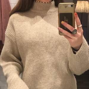 Detta är en beige stickad tröja som är köpt på hm. Den jag vita pärlor fast sydda vid halsen.