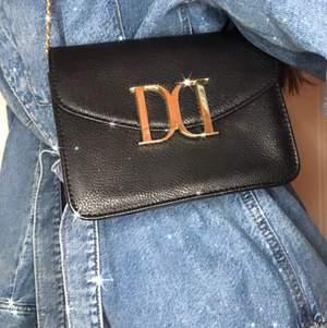 Stilren Don Donna väska. Svart med guldiga detaljer som bildar en stilig detalj på looken. Guldigt långt kedje band, MEN som går att knyta på insidan till valfri längd utan något synligt. Helt i nyskick🖤