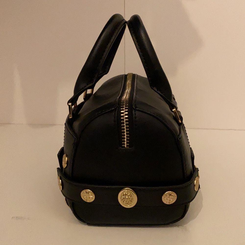En mindre svart bowler väska med guld detaljer från Topshop. Det finns ett ytterfack, samt en korthållare i huvudfacket. Är i topp skick! B:14L:20H:14 (cm). Väskor.
