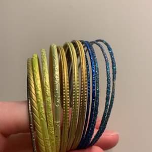 Metallarmband i olika färger. 3 st blå med glitter och tre i färgad metall = 25kr, 7 st gul/vit/brons = 35kr, en i silverfärgad metall ingår med valfri av de andra. Man behöver givetvis inte köpa alla och kan välja mellan de man tycker är snyggast. Rabatt om man köper flera set
