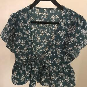 Blusen är inte använd och är super söt. Den är mörkgrön med vita små blommor.