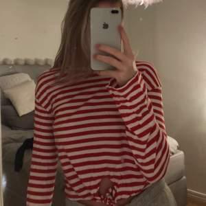 Vit och röd randig långärmad tröja med knytning längst ner.