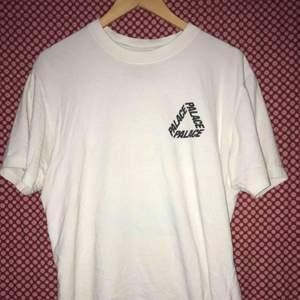 """T shirt från det brittiska skatemärket Palace. Tröjan är vit med klassisk """"tri-logo"""" i mariblå på både bak- och framsidan av plagget.  Nyskick 10/10 condition. Kontakta mig om ni har frågor eller vill se mer bilder."""