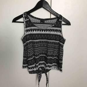 ett mönstrat linne från ginatricot 🖤 man knyter det längst ner som man själv vill. använt några få gånger. frakt tillkommer!