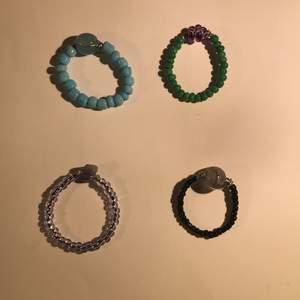 Ringar lila med Sten, grön med blomma, svart med marmor pärla, blå med marmor pärla. Alla kostar lika mycket:) kan göra dem till just din storlek