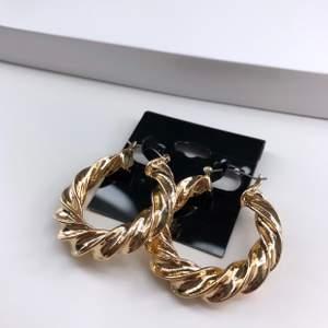 Guldfärgade runda örhängen ifrån Asos med en tjock slingrande design. Helt oanvända!