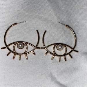 Ett par guldiga örhängen med en pärla i mitten. (De finns inga ploppar man sätter bak på örat)