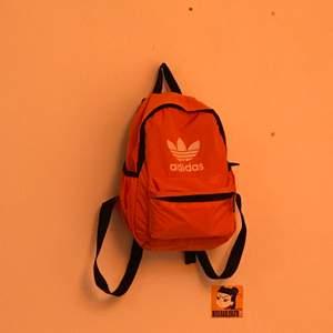En mini Adidas ryggsäck i neonorange färg. Ingen aning om det är fejk eller äkta. Använd 1 gång och är så gott som ny. Säljer för 90kr + frakt🧡🧡 Priset går att diskuteras.
