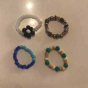 4 st pärlade ringar. De passar på fingrar i både S och M men de två nedersta sitter lite tajtare om man har M. Alla är gjorda på elastisk tråd, så de är enkla att ta av och på. 1st för 20kr eller 4st för 60kr