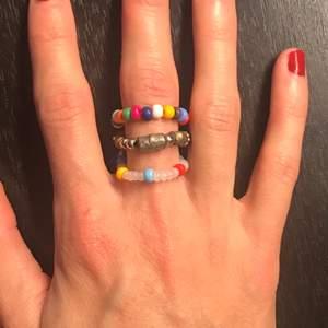 3 ringar i en!! En ring med 3 ringar i olika mönster och färger. Skitball!! Om det syns dåligt så är mitten ringen gjort av pärlor i metall. Skulle säga att den är i storlek M, men den är elastiskt så kanske går på L också och kan sitta lite löst på S.