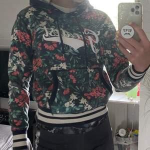 En snygg hoodie med rosor och text. Superskönt material som är lagom luftigt. Inte för tajt eller liten även fast den är XS