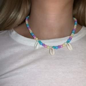 Flerfärgat pärlhalsband med snäckor🤍💞🐚💙💜💛 halsbandet försluts med lås och tråden är elastisk