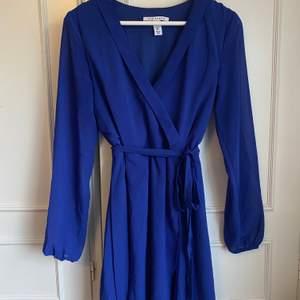 En blå fin klänning med ett snöre i midjan. Köpte den förra sommaren och aldrig använd, så den är i nyskick.