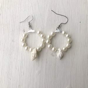 Egentillverkade örhängen i vita pärlor med vita snäckor i mitten.