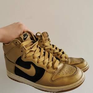 Nike air Jordans/dunks i guld och svart i gott skick, några år på nacken men inte särskilt använda. Dam, storlek 38 (US 7).