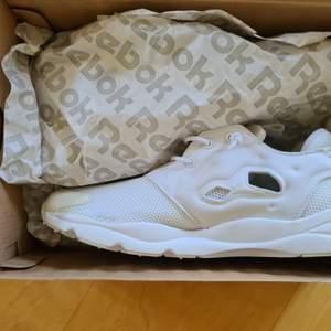 Oanvända Reebok Classic Furylite sko. Kan användas som running/träningssko/sneakers. En trendig och skön sko i färgen vit med ovansida i textil och sulan i gummi. Nya. Unisex. Strl 37,5. På grund av flytt och för många oanvända skor säljer jag dessa. Ordinarie pris 849,- Mitt pris 400,-. Köparen står för frakten.
