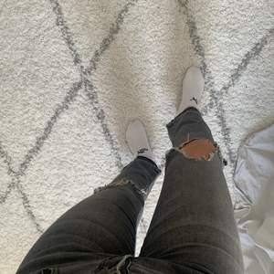 Ett par supersnygga gråa jeans från zara med slitningar på knäna och nertill.