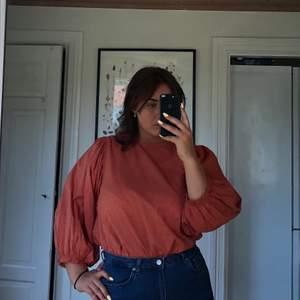 Peach/orange blus från Gina Tricot. Fin i passformen med puffarmar och fin knäppning i ryggen, se bild tre. Luftig och perfekt för sensommar kvällar. Max använd två gånger, så i väldigt bra skick. Nypris 250, köpare står för frakt.