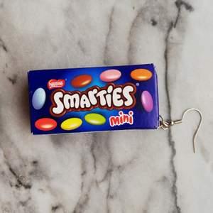 Ett örhänge med en (tom) mini smarties kartong