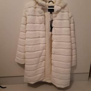 Helt ny fuskpäls kappa från Amisu. Härlig vit färg. Luva. Går att stänga med knappar. Strl 36 men passar 38 också. Fraktar men kostnad tillkommer.