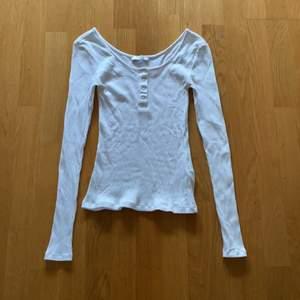 En vit långärmad tröja med knappar