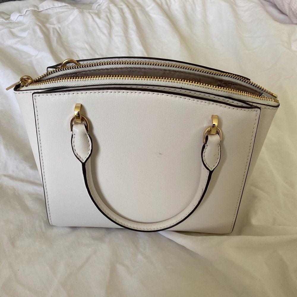 Liten vit axelbandsväska från Michael Kors. En längre rem tillkommer (den som ligger i väskan). . Väskor.