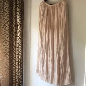 Nude/ljusrosa långkjol från Zara Trf. Siden-aktigt material och resår i midjan. Lång slits och med kort underkjol i trikå. Storlek S. Fint skick. Köparen står för frakt!
