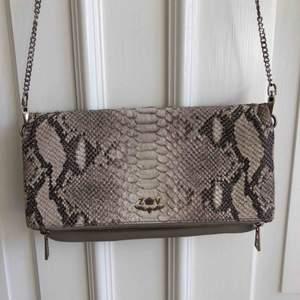 Jag säljer en ormskinns väska från Zadig&voltaire med tillhörande långt axelband  Köpt för: 3600kr
