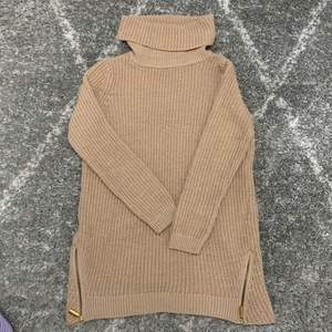 Längre stickad tröja i beige med hög krage och guldkedjor längst ned vid varje sida. Super skön!