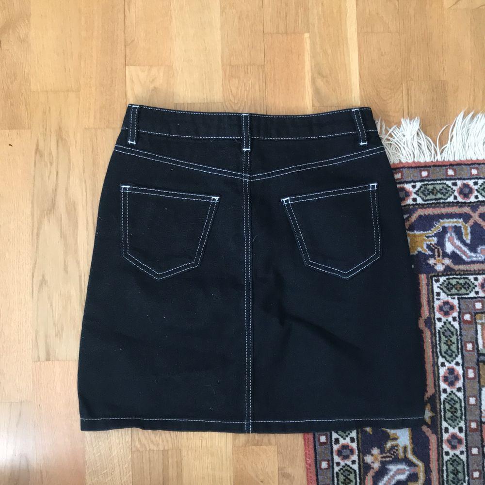 svart jeanskjol med vita kontrastsömmar. köpt från new look. använd ett fåtal gånger men i superbra skick. . Kjolar.