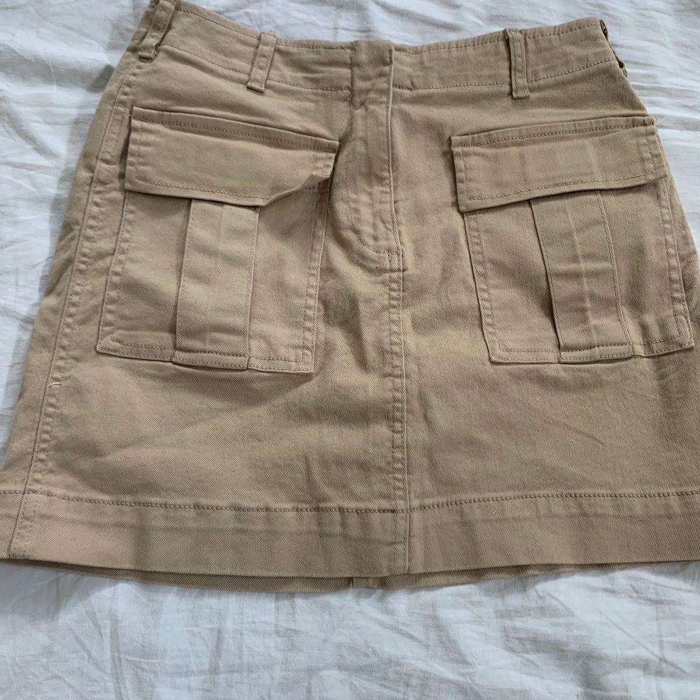 Säljer min kjol från Gina Tricot som är beige med fickor där fram, kjolen är bara använd få gånger . Kjolar.