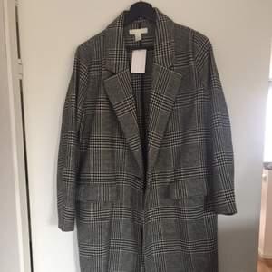 Helt ny rutig kappa från H&M. Prislapp kvar. Tunnare kappa som passar höst/vår. Frakt tillkommer på 53kr.