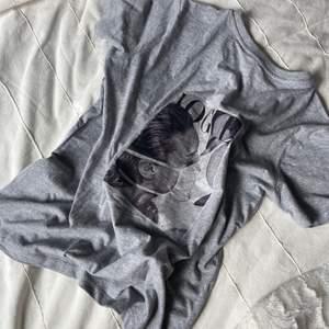 Grå t-shirt med tryck på. Storlek S och den är oversized i storleken