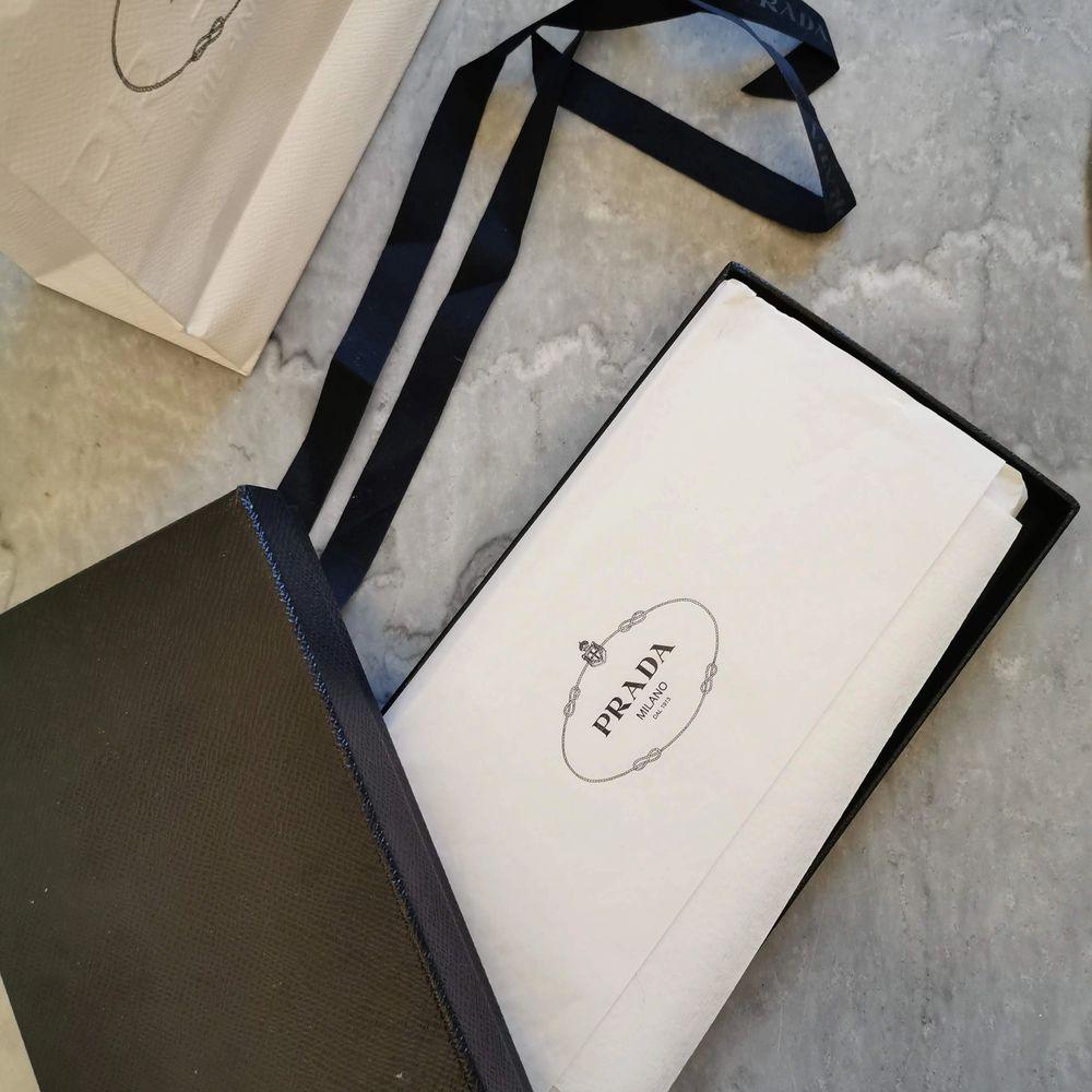 Hel ny och oanvänd plånbok från Prada i den lyxiga färgen röd.  Det är en gåva som aldrig har kommit till användning och endast legat nedpackad i sin kartong.  Inköpt på Prada birger jarlsgatan i Stockholm.  Kvitto, presentkartong, snöre, papper och påse . Accessoarer.