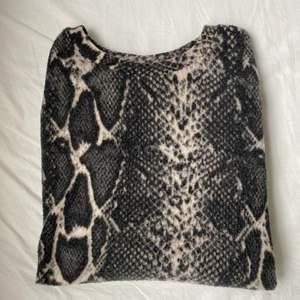 En långärmad tröja från Gina Tricot som inte används längre, ormmönster på tröjan. Väldigt mjuk & skön.