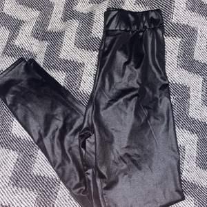 Svarta byxor i glansigt material, typ samma stil som skinnbyxor. Resår i midjan inte använda.