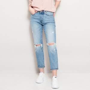 Mom/boyfriend jeans som är slitna, korta i modellen. Modell wide.