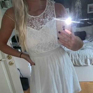 Oanvänd vit klänning med spets upptill och öppen rygg. 100:- eller bud! Köparen står för frakten! Endast Swish!