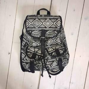 Svart- och vitmönstad ryggsäck från JFR med ett par olika fack. Toppskick, nypris typ 300-400