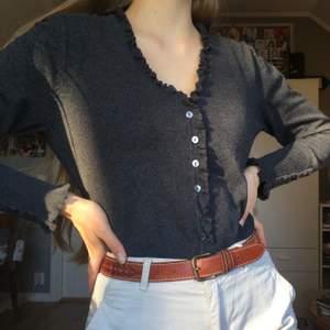 En tröja med knappar och fina detaljer runt kanterna. Den är från märket flash essential. Den är både fin att använda knäppt eller uppknäppt över någonting annat. Det står storlek L på lappen men jag anser att det snarare är en M. FRAKTEN INGÅR!!