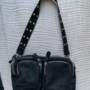 """Säljer denna nya väska, endast använd vid ca 4 tillfällen. Inga skavanker eller slitningar då den är ny. Med följer ett kort band med """"nitar"""" på och ett långt. Skriv för mer info (kan även tänka mig att byta mot vad som)"""