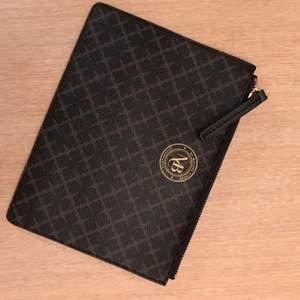 Clutch svart/brun från Malene Birger i klassiskt mönster. Oanvänd - Nyskick!!!   Storlek: B 25 x H 17 cm