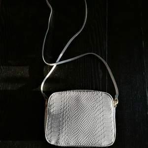 Liten men rymlig ljusgrå axelbandsväska i snake / orm mönster, endast använd under ett enstaka tillfälle i någon timme.🐍 Finns ett litet inre fack i väskan. Liten fraktkostnad tillkommer
