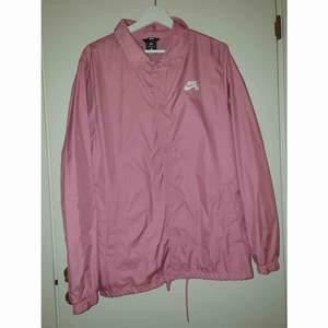 Coach jacket från Nike. Rosa i storlek M, knappt använd därav väldigt fint skick. Rak i modellen, två fickor nedtill med knappar. Köparen betalar frakten.