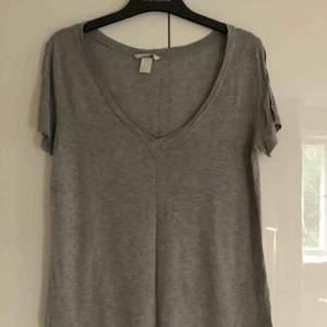 Ljusgrå v-ringad T-shirt från Hm. (Bilden blev lite mörk). Fint och klassiskt basplagg i bra skick. Strl S men sitter mer som en M